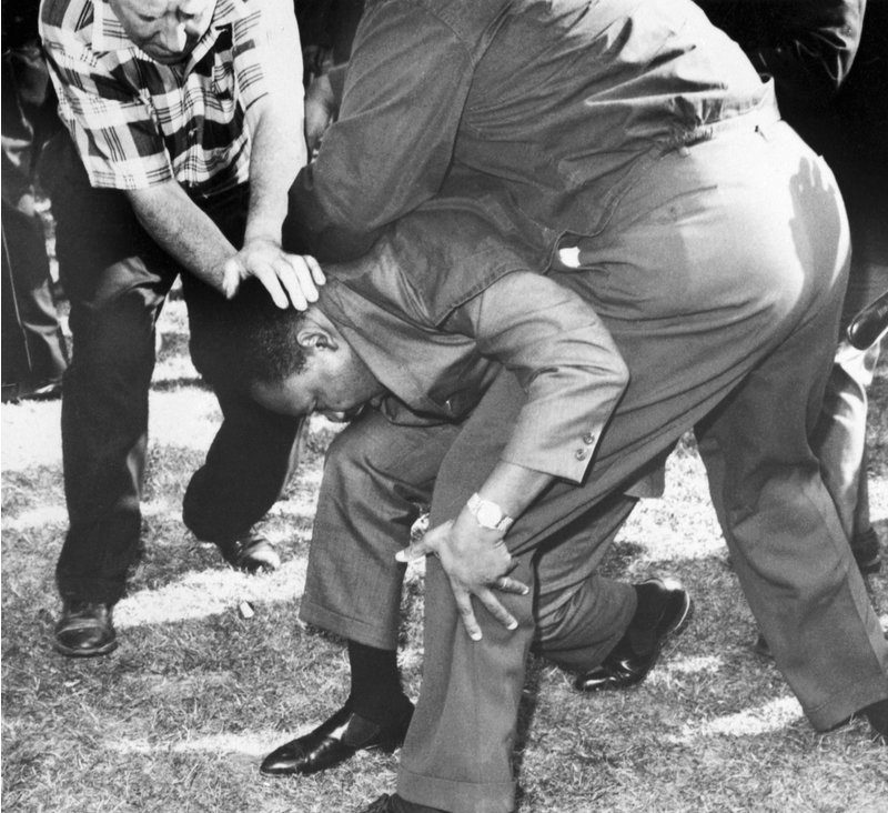 Struck on the head by a rock thrown by a group of hecklers, MLKfalls to one knee | Credit: Bettmann/Getty Images
